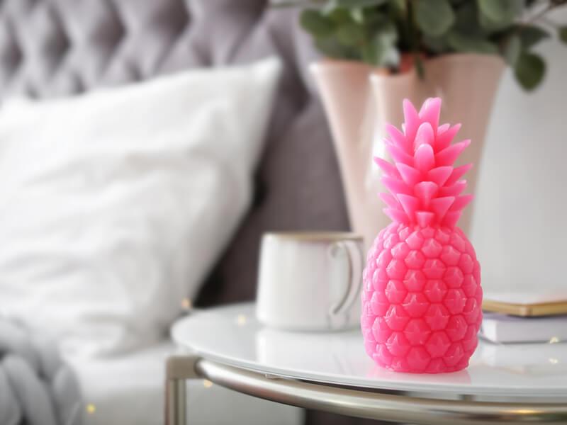 Bougie d'ananas rose sur la table de chevet