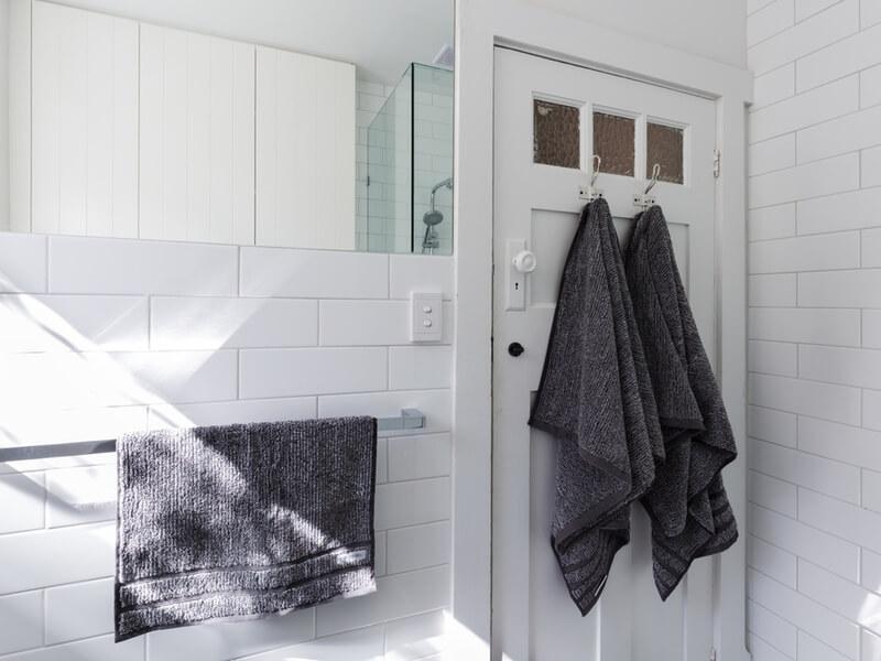 Salle de bain blanche avec des serviettes à la porte