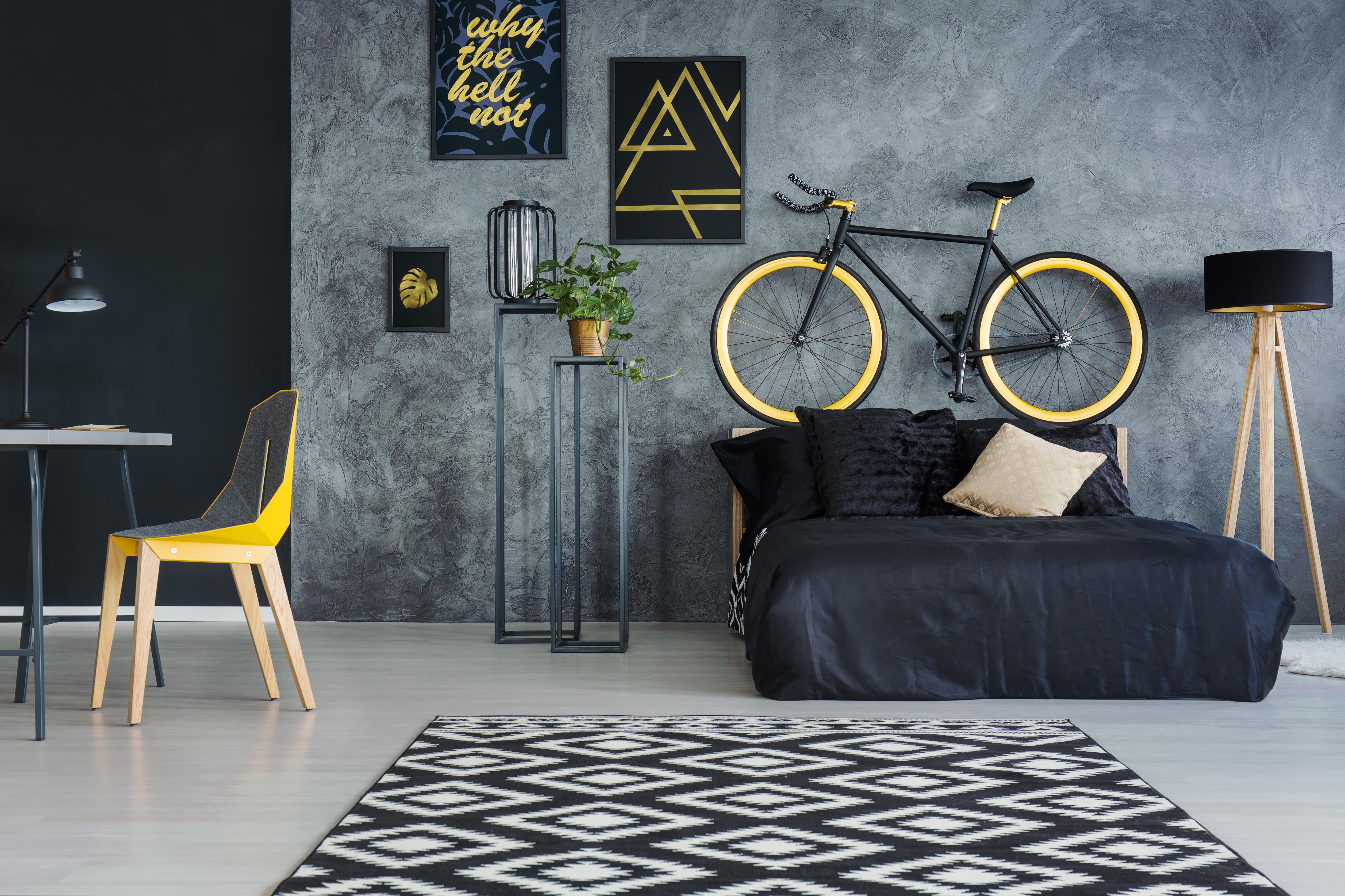 Chambre grise avec vélo sur mur et tapis de diamants