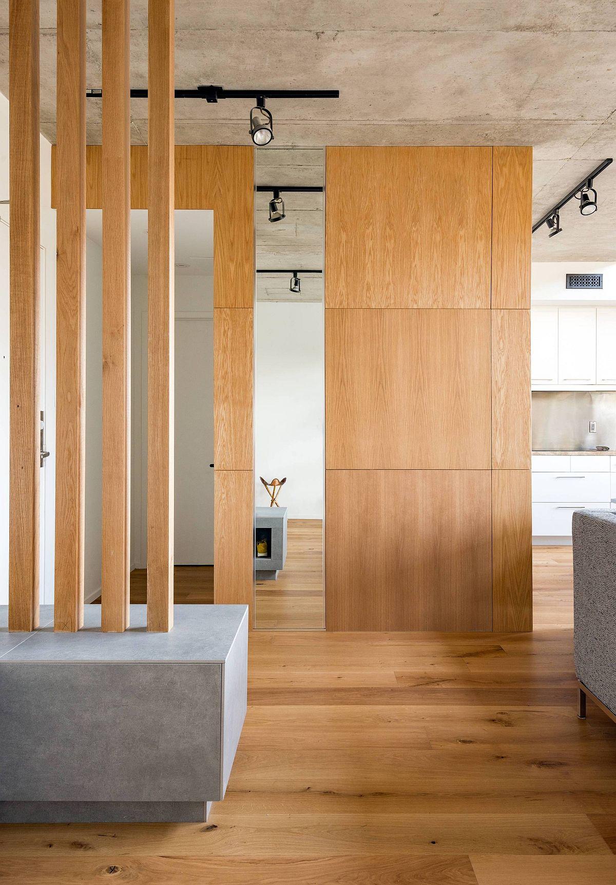 Des écrans et des cloisons en bois personnalisés délimitent l'espace à l'intérieur du salon décloisonné