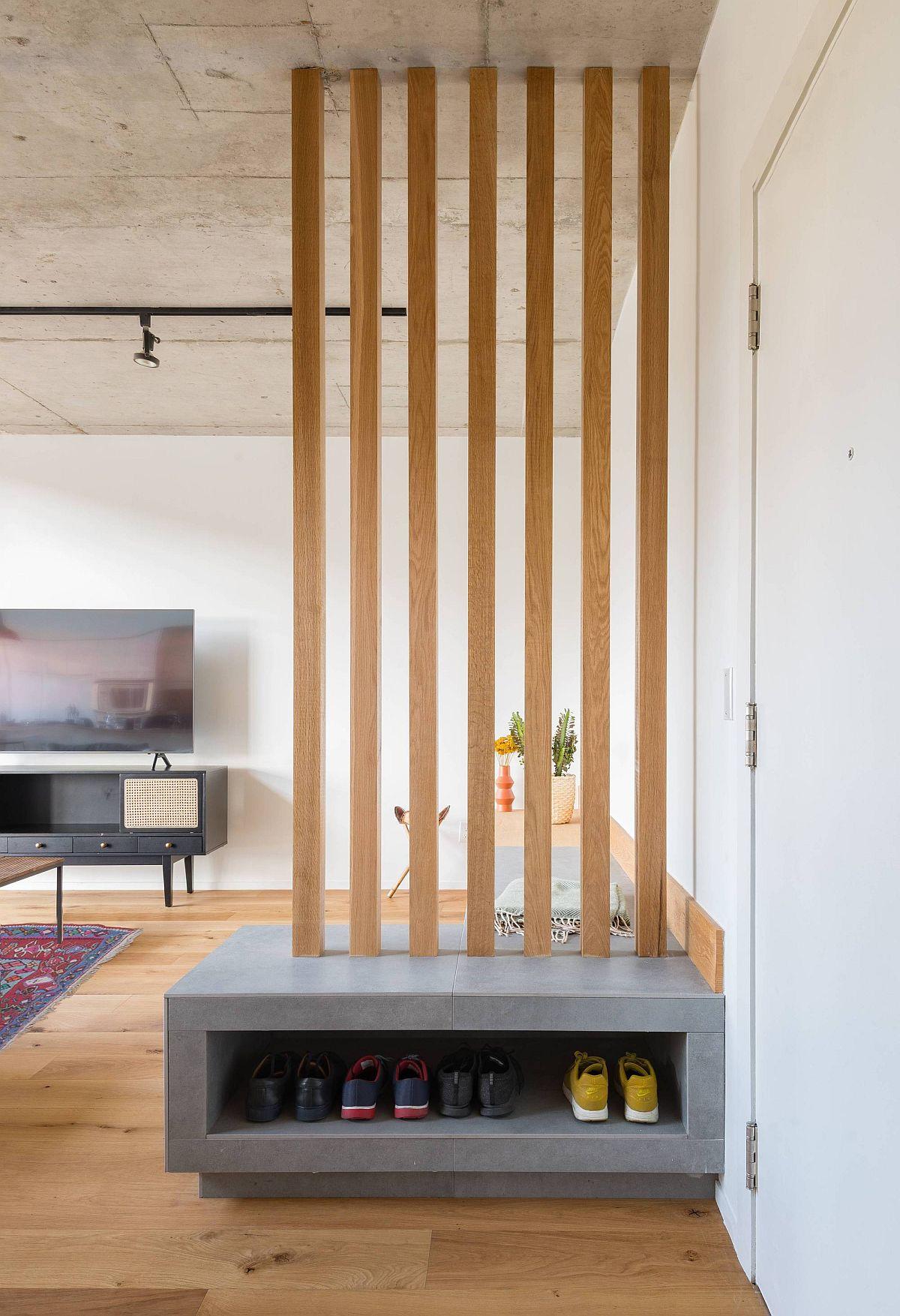 Les lattes en bois ainsi que le banc personnalisé dans le salon offrent également un espace de rangement pour les chaussures pour l'entrée