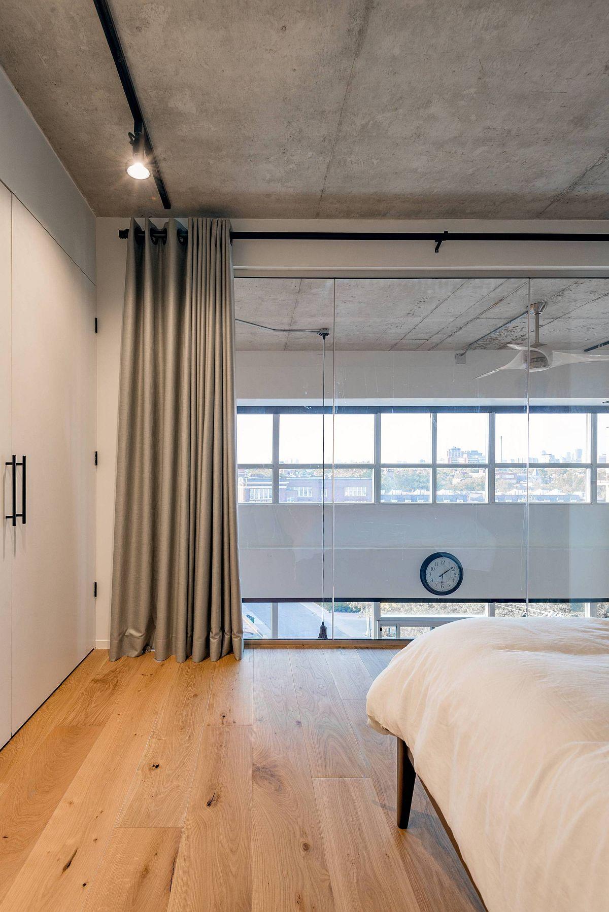 Chambre moderne avec parquet, plafond en béton et rideaux gris