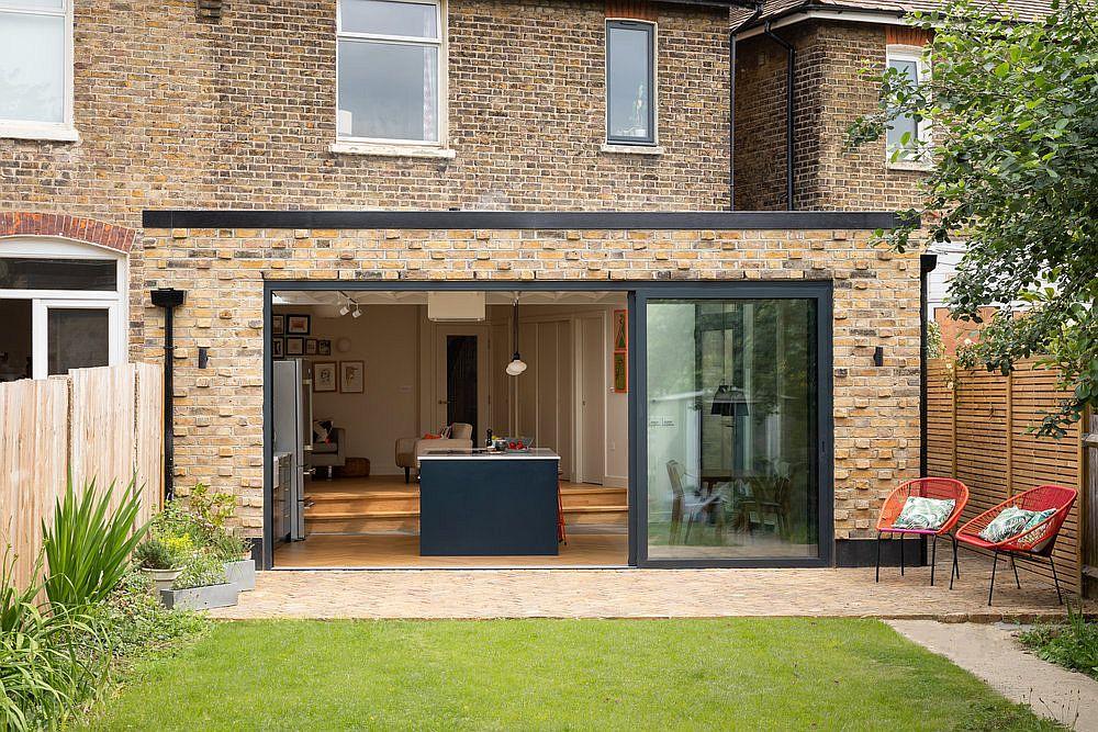 Les portes coulissantes en verre relient la cuisine à un magnifique nouveau jardin à l'extérieur