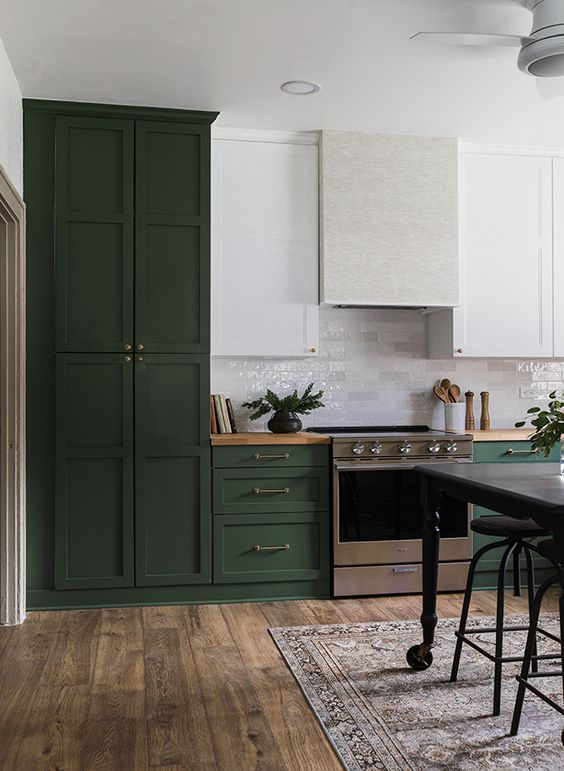 une belle cuisine vert foncé et blanche de style vintage, avec une hotte neutre et des comptoirs de boucherie est chic