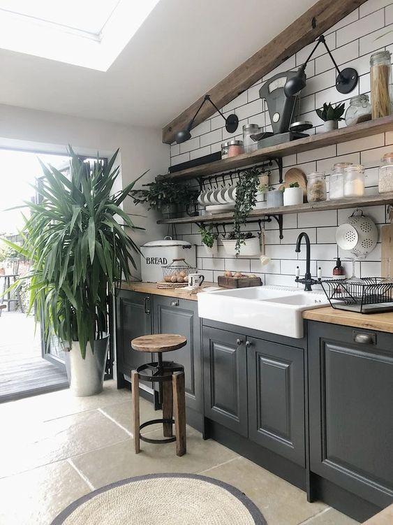 une cuisine moderne et audacieuse en noir, des comptoirs en bloc de boucherie, un dosseret de carreaux de métro blanc et de la verdure en pot ainsi que des étagères ouvertes