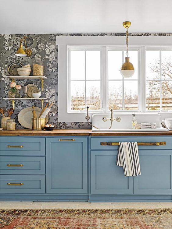une belle cuisine bleue à un mur avec du papier peint floral, des comptoirs de boucherie et de jolies suspensions vintage