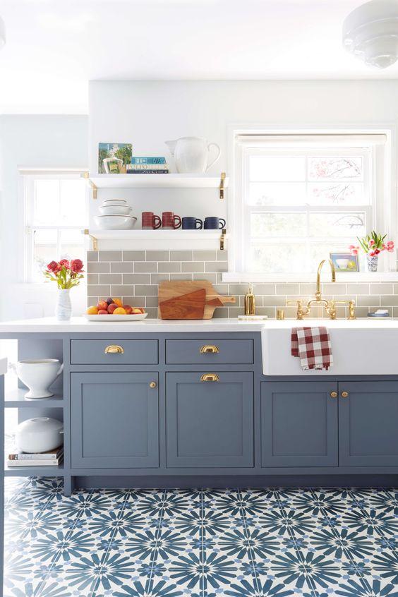 une cuisine bleue à un mur avec un dosseret de carreaux de métro gris et un sol en carrelage bleu imprimé plus des touches dorées est wow