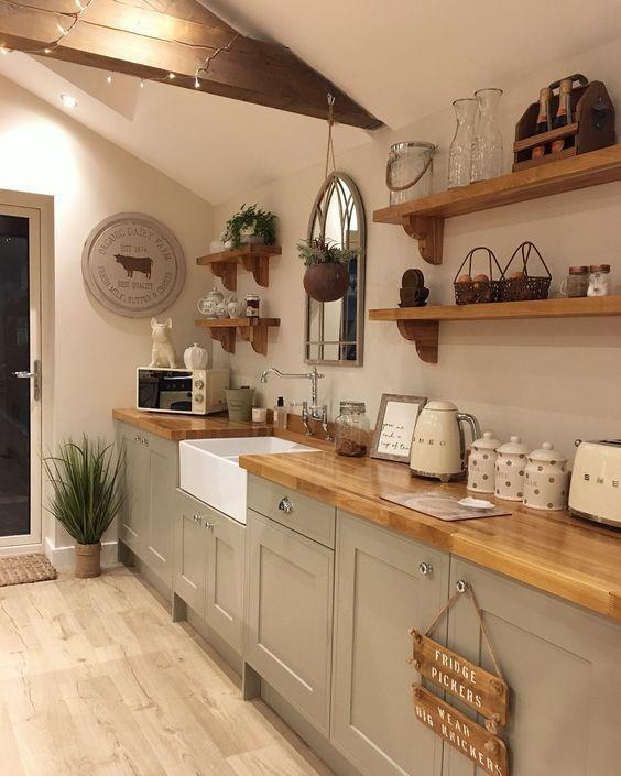 une cuisine chic à un mur gris avec des comptoirs de boucherie, des étagères ouvertes et de la verdure en pot ainsi que des lumières