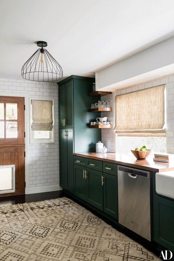 une cuisine de ferme vert foncé chic avec un comptoir en buctcherblock, des abat-jours tissés et des suspensions en métal plus un tapis boho