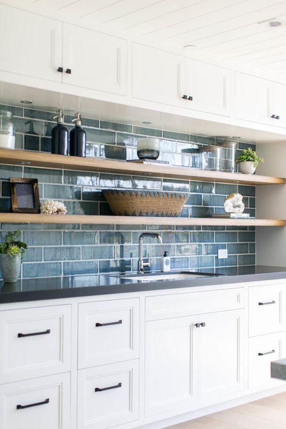 une cuisine chic avec des armoires blanches, des étagères ouvertes, un dosseret de carreaux bleus est un espace de ferme chic avec une touche de décor côtier