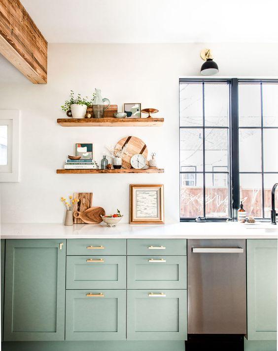 une cuisine verte chic de style ferme, un comptoir en pierre blanche et des étagères ouvertes, des poutres en bois et une fenêtre avec un cadre noir
