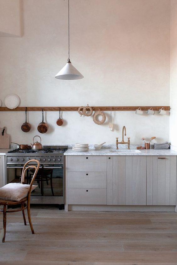 une cuisine chic en bois blond à un mur avec un comptoir en pierre blanche et un long support avec des tasses et des casseroles