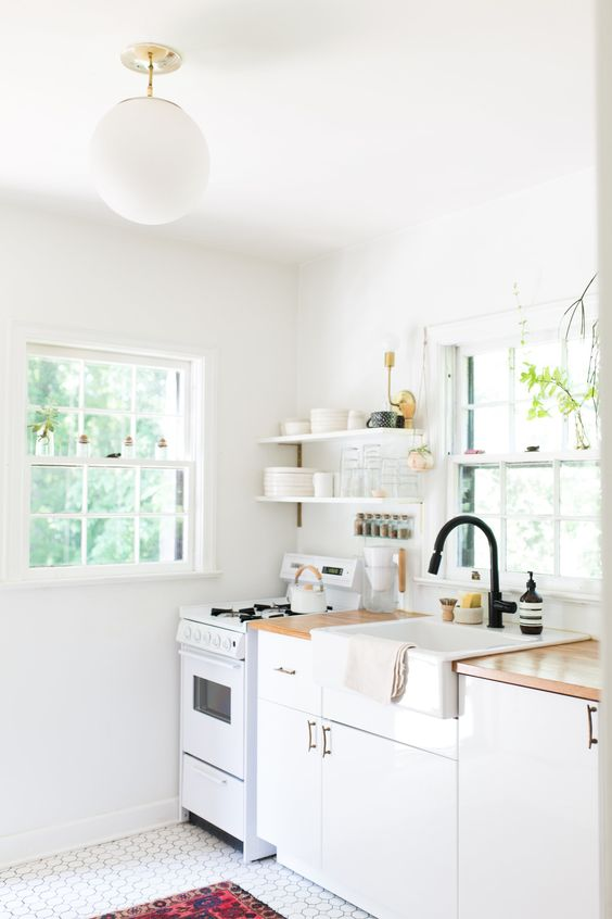 une cuisine chic à un mur blanc avec des comptoirs en bloc de boucherie et des luminaires noirs, un sol carrelé et un tapis audacieux