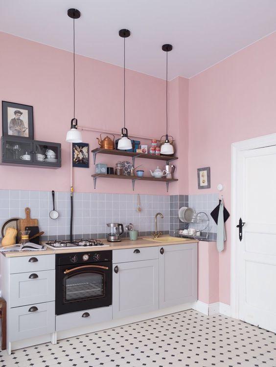 une cuisine grise confortable et mignonne à un mur avec un comptoir de boucherie blonde et un dosseret de carreaux gris et des lampes suspendues