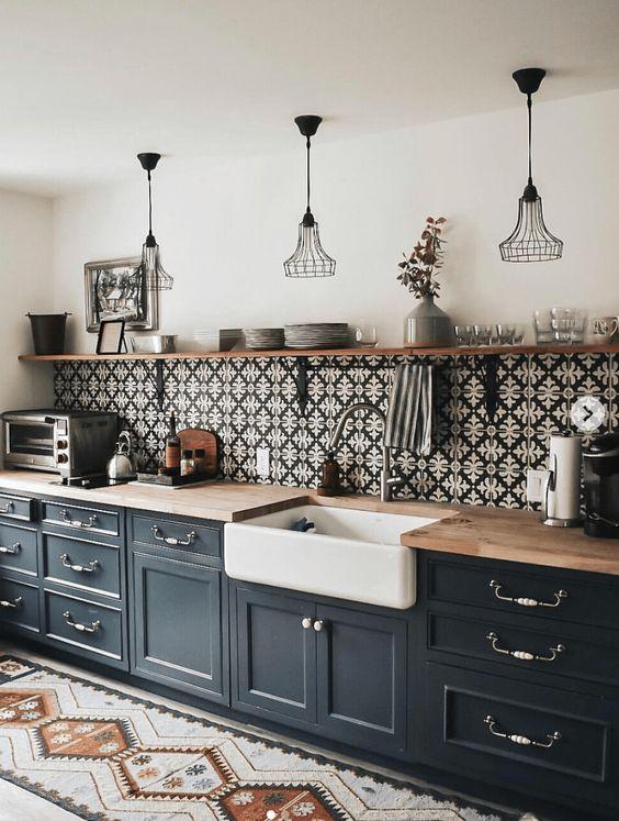 une cuisine noire à un mur moderne du milieu du siècle avec des comptoirs de boucherie, un dosseret de carreaux à motifs et des suspensions en métal