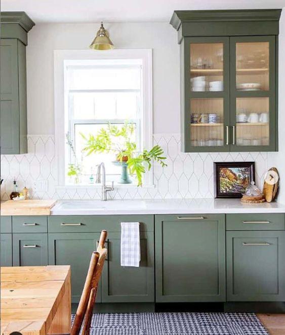 une cuisine verte à un mur avec un joli dosseret de carreaux blancs, un comptoir blanc et des touches de laiton plus un tapis imprimé