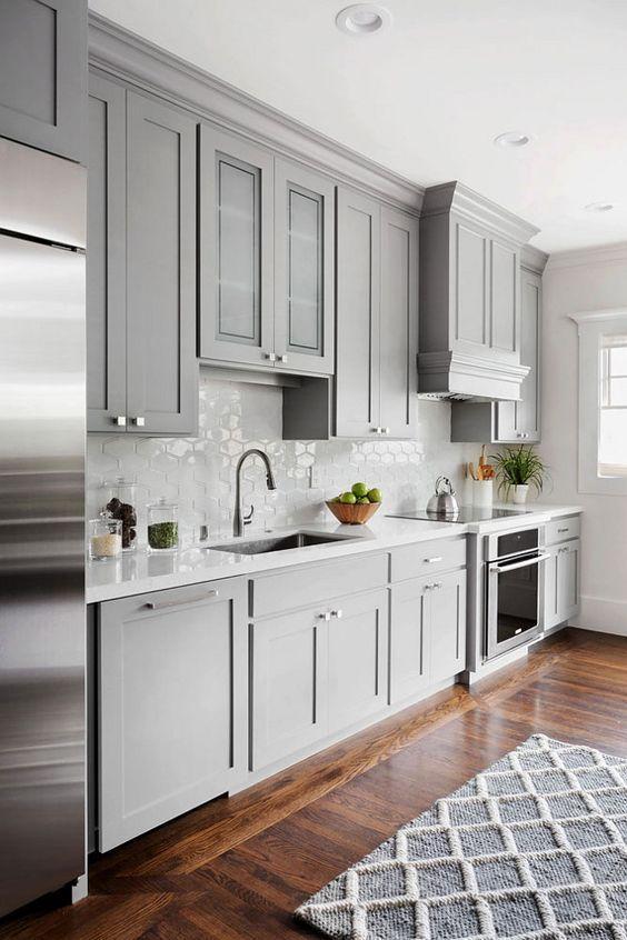 une cuisine gris clair avec un dosseret de carreaux hexagonaux et des appareils électroménagers en acier inoxydable est une idée chic et jolie