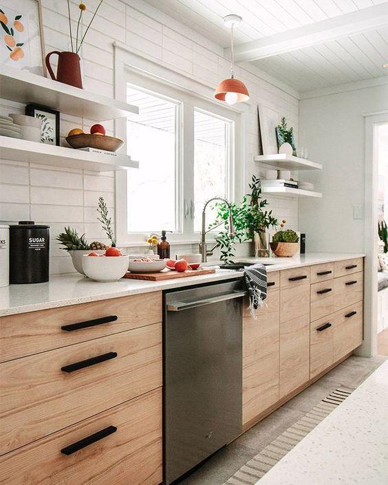 une cuisine en bois blonde moderne du milieu du siècle avec des étagères ouvertes, des poignées noires et un dosseret de carreaux maigres