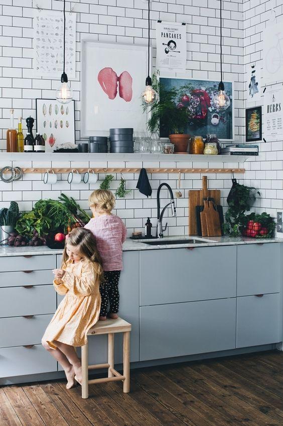 une cuisine bleu clair à un mur avec un dosseret de carreaux de métro blanc, un comptoir en pierre blanche et des étagères et des ampoules