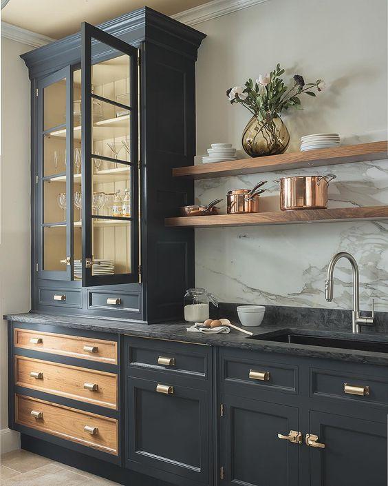 une cuisine vintage gris graphite avec des poignées dorées, un comptoir en pierre noire et un dosseret en pierre blanche