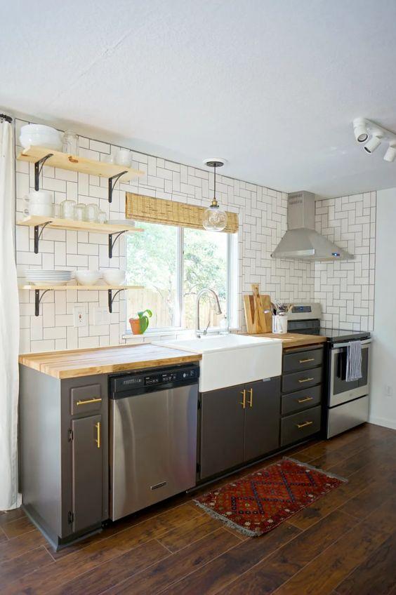 une cuisine grise moderne du milieu du siècle avec des étagères ouvertes, un dosseret de carreaux blancs et des comptoirs en bloc de boucherie est un espace chic
