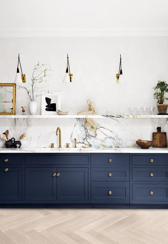 une cuisine marine à un mur avec un dosseret et des comptoirs en pierre blanche, une étagère en pierre et des appliques est super chic