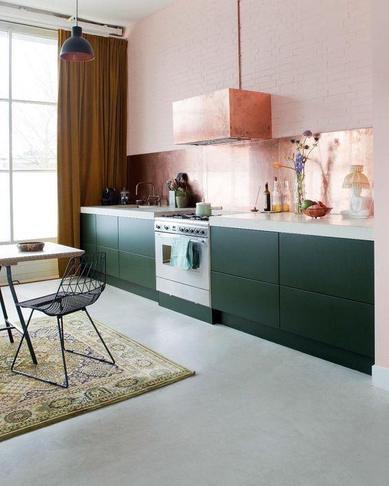 une jolie cuisine à un mur vert foncé avec un comptoir en pierre blanche, un dosseret en or rose et une hotte assortie
