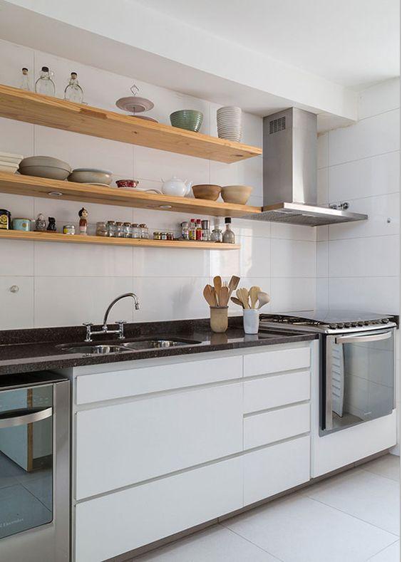 une cuisine blanche minimaliste avec des comptoirs en pierre noire et des étagères ouvertes est une idée chic et élégante
