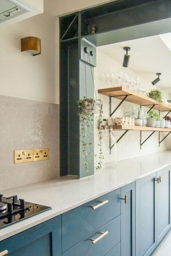 une cuisine bleu marine à un mur avec un dosseret et des comptoirs de carreaux de métro blancs, des étagères en bois blond ouvert et de la verdure