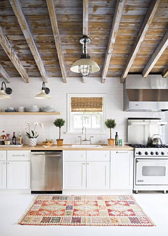 une jolie cuisine à un mur avec des armoires blanches, des comptoirs de boucherie et un plafond shabby chic est très accueillante
