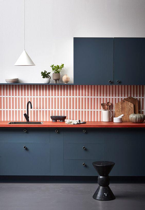 une cuisine marine raffinée à un mur avec un dosseret de carreaux skinny orange, un comptoir orange et une suspension blanche