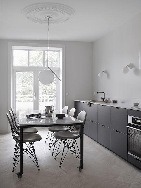 une cuisine scandinave noire à un mur avec un plan de travail blanc et des luminaires noirs ainsi que des appliques et une suspension