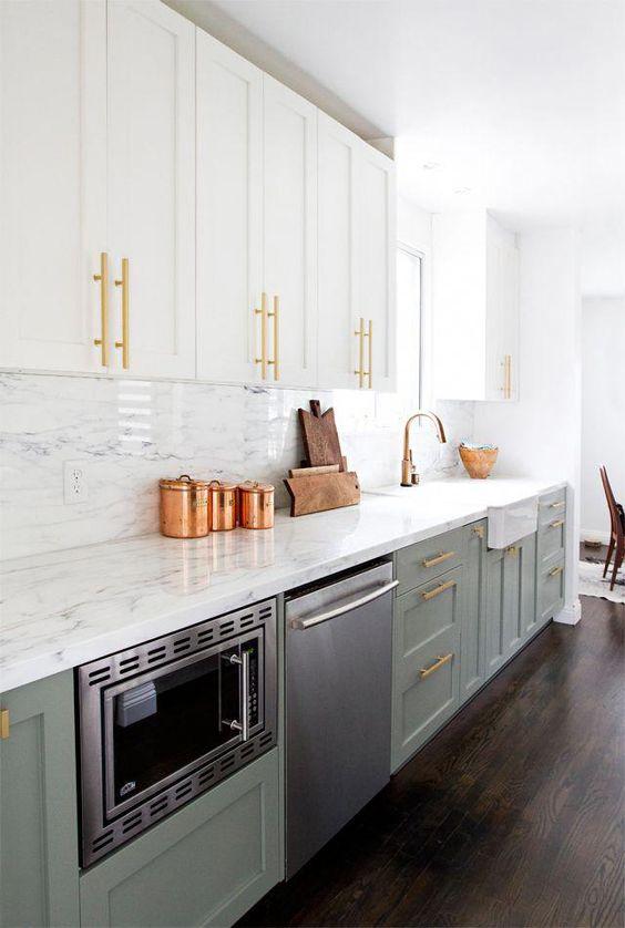 une jolie cuisine à un mur bicolore en blanc et vert olive, avec des comptoirs en pierre blanche et un dosseret et des poignées en or