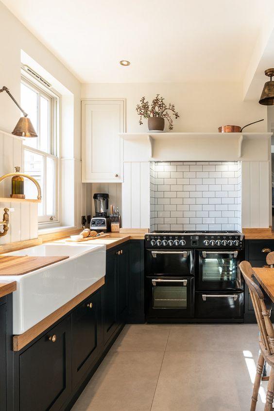 une cuisine de ferme noire en forme de L avec des comptoirs de boucherie, un dosseret de carreaux blancs et de jolies lampes vintage est cool