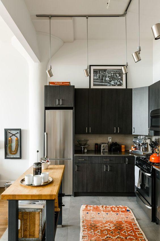 une cuisine noire en forme de L avec un dosseret de carreaux, un petit îlot de cuisine avec un comptoir en bloc de boucherie et des suspensions