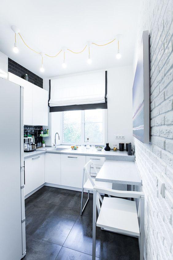 une cuisine scandinave noir et blanc avec un dosseret noir et une petite zone de restauration