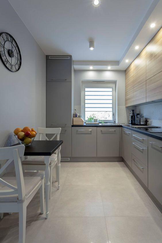 une cuisine contemporaine teintée de gris et de lumière avec des comptoirs noirs et un petit espace à manger