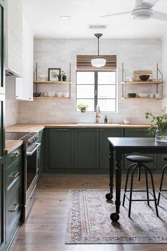 une cuisine en forme de L verte et blanche audacieuse avec des comptoirs de boucherie, des étagères ouvertes et des touches de laiton est très confortable