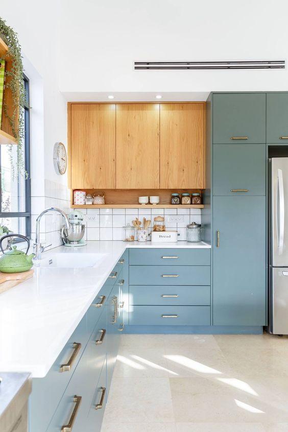 une cuisine bleue et tachée de lumière avec un comptoir blanc, un dosseret de carreaux blancs et des poignées en or et en laiton