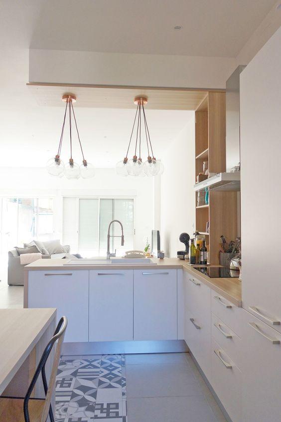 une cuisine contemporaine en forme de L blanche avec comptoirs de boucherie et étagères en bois, avec lampes suspendues