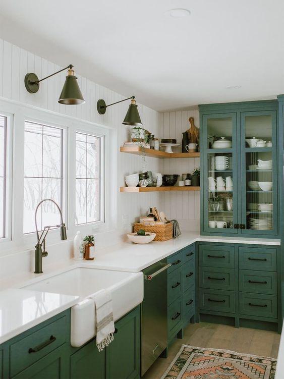 une cuisine de ferme verte avec une armoire en verre, des comptoirs en pierre blanche et des poignées noires est un espace chic