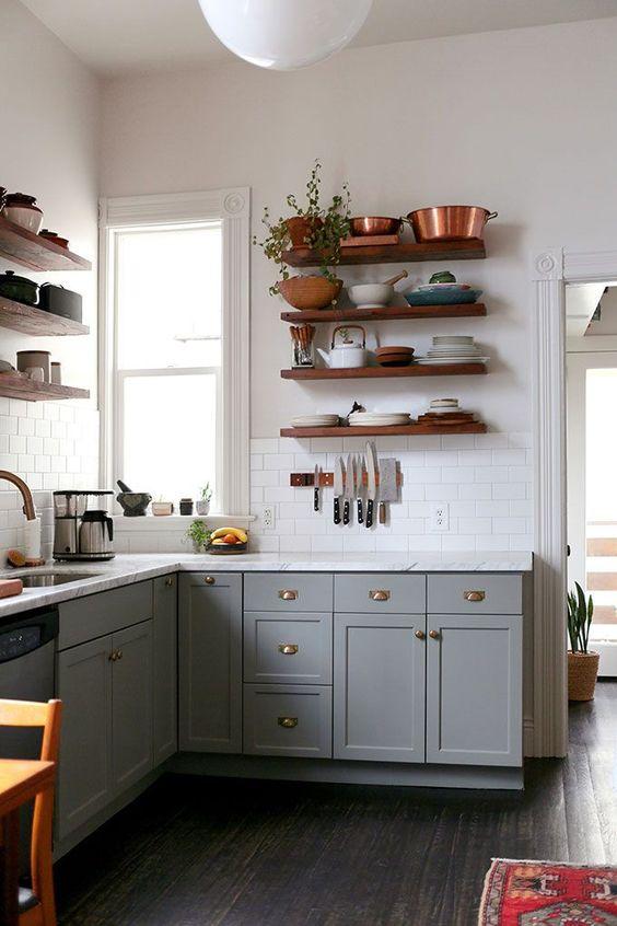 une cuisine en forme de L boho gris avec des étagères ouvertes, un comptoir en pierre blanche et un dosseret de carreaux blancs plus de la verdure