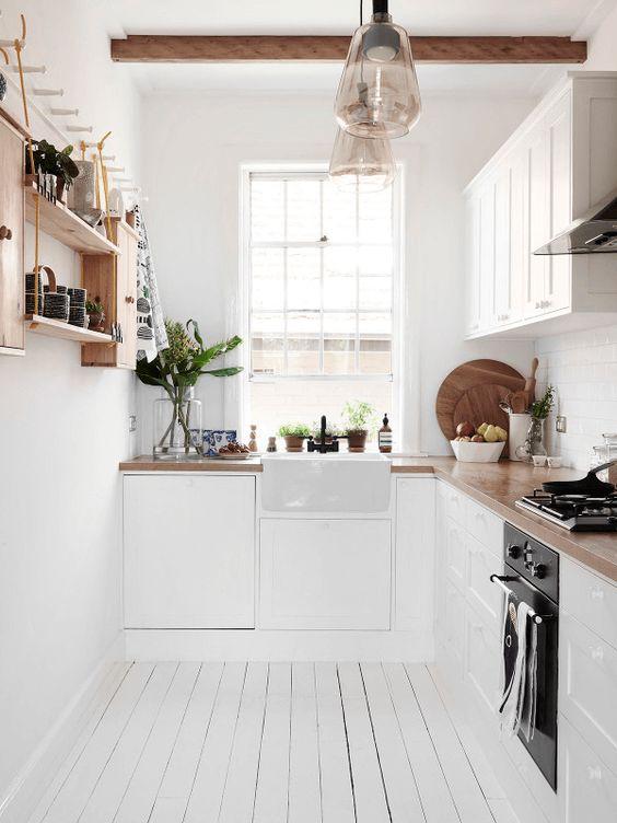 une cuisine scandinave en forme de L avec des comptoirs de boucherie, des étagères ouvertes et des poutres en bois