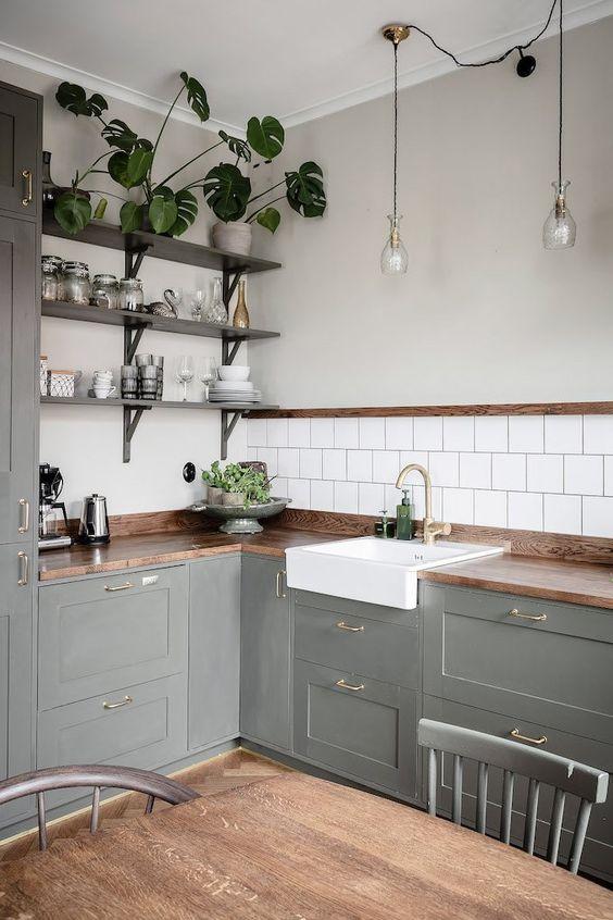 une cuisine rustique grise en forme de L avec des comptoirs de boucherie, des étagères ouvertes et de la verdure en pot ainsi que des suspensions
