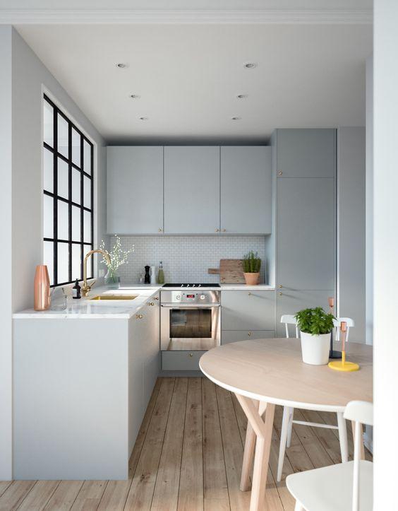 une cuisine contemporaine grise avec des comptoirs en pierre blanche, une porte-fenêtre et une table ronde