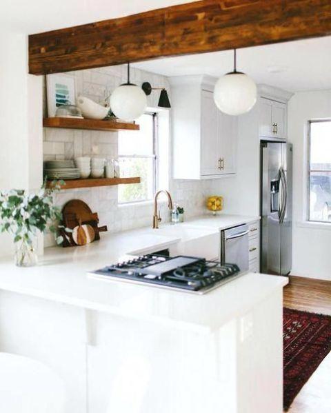 une cuisine de ferme blanche confortable avec un dosseret en marbre blanc et une poutre en bois est très accueillante