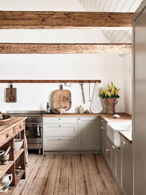 une cuisine gris clair avec comptoirs de boucherie et poutres en bois, un îlot de cuisine en bois et un plancher en bois
