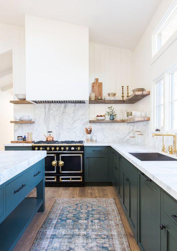 une grande cuisine en forme de L bleu marine et blanc avec des comptoirs en pierre blanche et un dosseret et un îlot de cuisine assorti