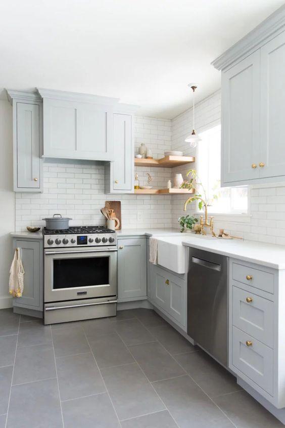 une cuisine en forme de L gris clair avec des étagères ouvertes, un dosseret de carreaux blancs et des poignées dorées est un espace très élégant et confortable