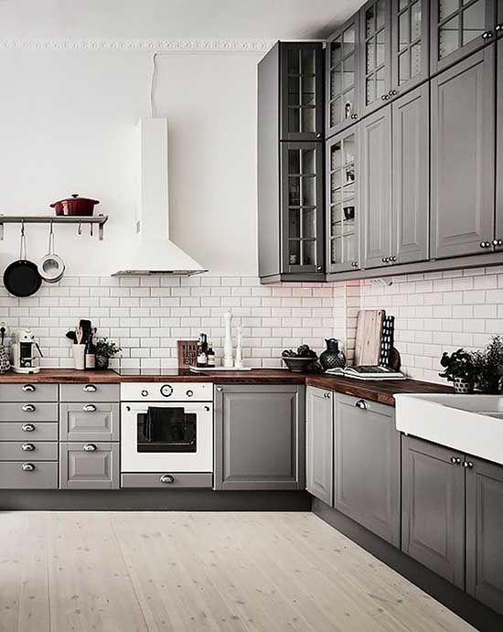 une cuisine scandinave grise avec des comptoirs de boucherie riches en couleurs et un dosseret de carreaux blancs ainsi que des appareils électroménagers blancs